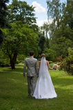 Bride and groom walking in a park Stock Images