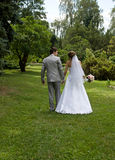Bride and groom walking in a park Stock Photography