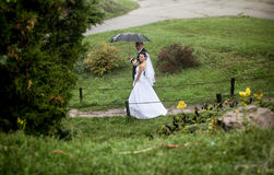Bride and groom walking at park on rainy day Stock Photos