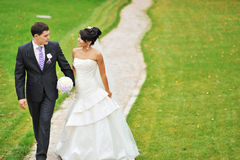 Bride and groom walking in a park together Stock Photos