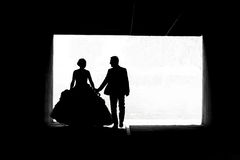 Bride and groom walking in passage bw Royalty Free Stock Photo