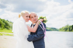 Bride and groom walking on the river Stock Images