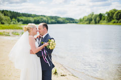 Bride and groom walking on the river Stock Photography