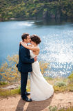 Bride and groom walking at the river Royalty Free Stock Photos