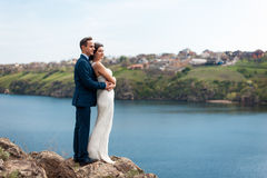 Bride and groom walking at the river Stock Photography