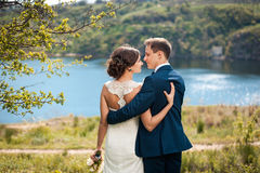 Bride and groom walking at the river Royalty Free Stock Images