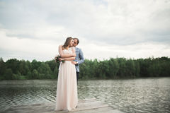 Bride and groom walking on the river, smiling, kissing Stock Photos