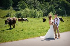 Bride and groom walking on the road Stock Photo