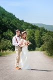Bride and groom walking on the road Stock Photography