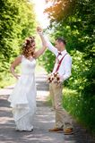 Bride and groom walking on the road. Out of town Stock Photography