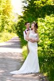 Bride and groom walking on the road. Out of town Royalty Free Stock Images
