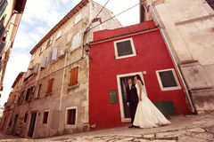 Bride and groom walking on streets Stock Photo