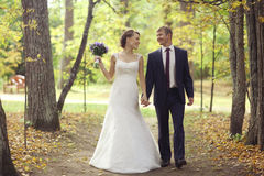 Bride and groom walking in summer park Royalty Free Stock Images