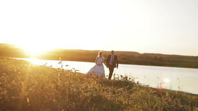 Bride and groom walking at sunset. Young family. the bride and groom are going to meet his future, his happiness, tenderly embracing each other at sunset stock video footage