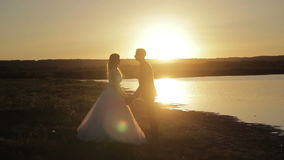 Bride and groom walking at sunset. Young family. the bride and groom are going to meet his future, his happiness, tenderly embracing each other at sunset stock footage