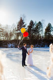Bride and groom are walking at the surface of frozen lake Royalty Free Stock Image