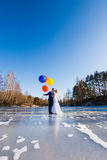 Bride and groom are walking at the surface of frozen lake Royalty Free Stock Photography