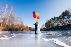 Bride and groom are walking at the surface of frozen lake Royalty Free Stock Photos