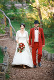 Bride and groom are walking to guests at banquet, arm in arm. Start wedding party. Decoration style, red marsala. Royalty Free Stock Photography