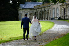 Bride and Groom walking to a Public Period House in Northern Ireland. Surrounded by green grass area Stock Photography