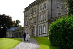 Bride and Groom walking to a Public Period House. In Northern Ireland surrounded by green grass area Stock Image