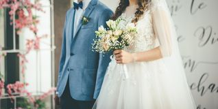 Bride and groom walking together with bouquet in hands stock photos