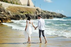 Bride and groom walking together holding hands near sea, Sperlonga Royalty Free Stock Image