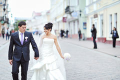 Bride and groom walking together in an old town Stock Images