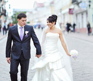 Bride and groom walking together in an old town Royalty Free Stock Image