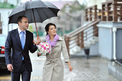 Bride and groom walking together in a rainy day Royalty Free Stock Photos