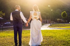 Bride and groom walking towards sunset holding hands Stock Image