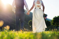 Bride and groom walking towards sunset holding hands Royalty Free Stock Images