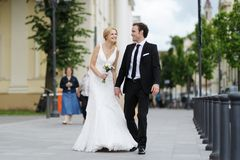 Bride and groom walking in a town Royalty Free Stock Photos