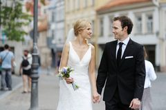 Bride and groom walking in a town Royalty Free Stock Image