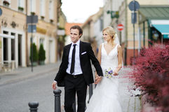 Bride and groom walking in a town Stock Photos