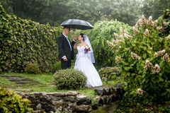 Bride and groom walking under umbrella at park Stock Images