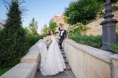 Bride and groom walking up the stairs in park. Bride and groom walking up the stairs in the park Stock Photo