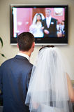 Bride and groom watch the video of his wedding Stock Images