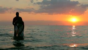 Bride And Groom In The Water. The groom sprinkles water on his bride. Against the backdrop of a beautiful sunset. Silhouettes stock video