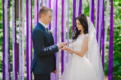The bride and groom wear each other at a wedding ceremony when rings on a background of multi-colored ribbons, love, marriage, rel Stock Photos