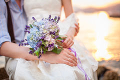 Bride and groom with wedding bouquet from lavender flowers and h. Ydrangea. Newlyweds sit by the sea at sunset Royalty Free Stock Photo