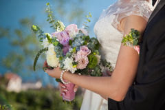 Bride and groom with wedding bouquet from roses, eucalyptus and. Dahlias, the bride is dressed in lace white wedding dress stock image