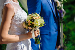 Bride and groom with a wedding bouquet for a walk Stock Photo
