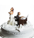 Bride and Groom on wedding cake. Angry bride because her husband doesn't leave the computer alone Royalty Free Stock Photos