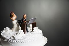 Bride and Groom on wedding cake. Angry bride because her husband doesn't leave the computer alone Royalty Free Stock Photo