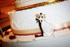Bride & Groom On Wedding Cake. Closeup of a miniature bride and groom on the base of a tiered wedding cake. Angled shot in horizontal format Royalty Free Stock Photos
