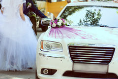 Bride and groom about wedding car decorated with flowers and rib Royalty Free Stock Photography