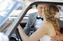 Bride and groom in a wedding car Stock Image