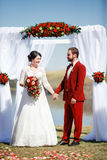 Bride and groom during wedding ceremon, arch flowers outdoors. Royalty Free Stock Photo
