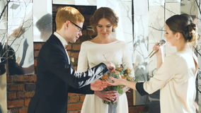 Bride and groom at wedding ceremony exchange ring each other while registrar talking stock video footage